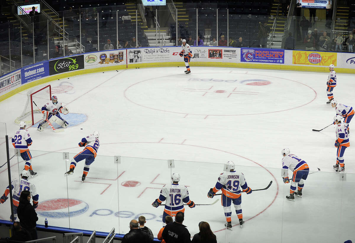 Sound Tigers goalie Kenny Reiter fields shots on goal from a circle of his teammates during pre-game warmups at the Webster Bank Arena in Bridgeport, Conn. on Sunday, November 24, 2013.