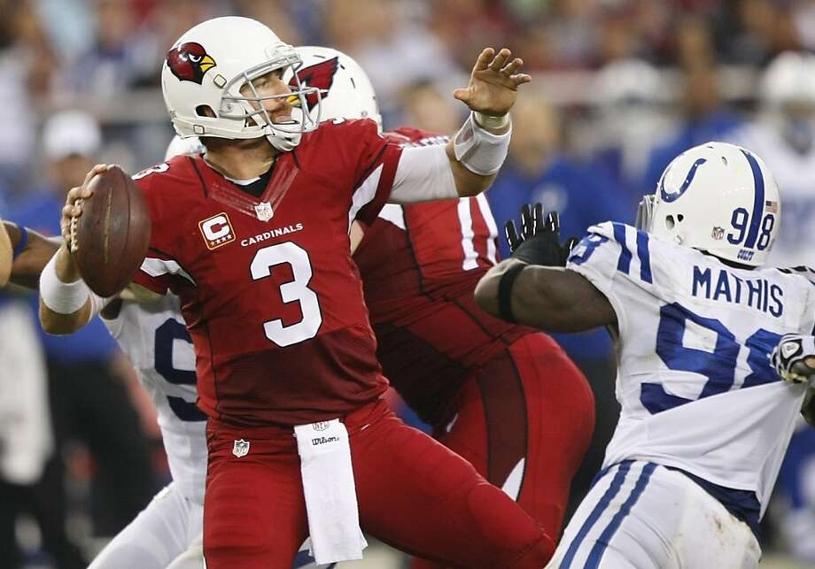 The Cardinals' Carson Palmer, who passed for 314 yards and two touchdowns, both to Larry Fitzgerald, braves pressure from the Colts' Robert Mathis. Photo: Rick Scuteri, Associated Press