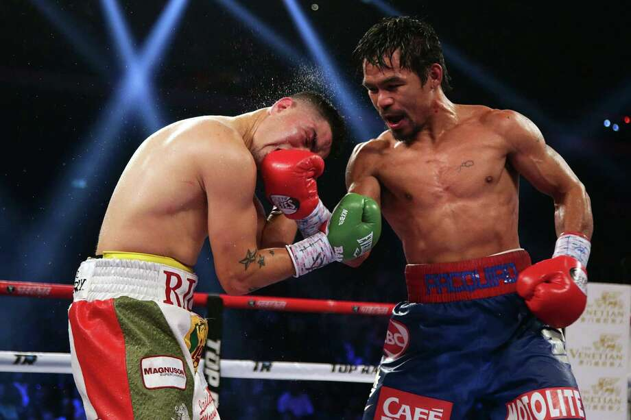 Manny Pacquiao (right) lands a right to the face of Brandon Rios late Saturday en route to a victory — his first after two consecutive losses. Pacquiao posted a unanimous decision. Photo: Nicky Loh / Getty Images