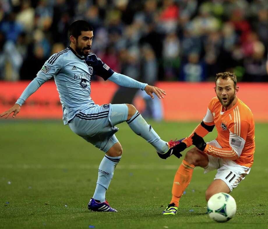 "Brad Davis, right, battling Sporting Kansas City's Paulo Nagamura on Saturday night, is proud of the way the Dynamo ""kept plugging away."" Photo: Jamie Squire, Staff / 2013 Getty Images"
