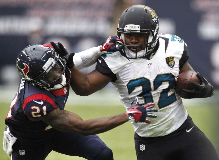 Jaguars running back Maurice Jones-Drew (32) is hit by Texans cornerback Brice McCain (21) on a run around the end during the second quarter. Photo: Brett Coomer, Houston Chronicle