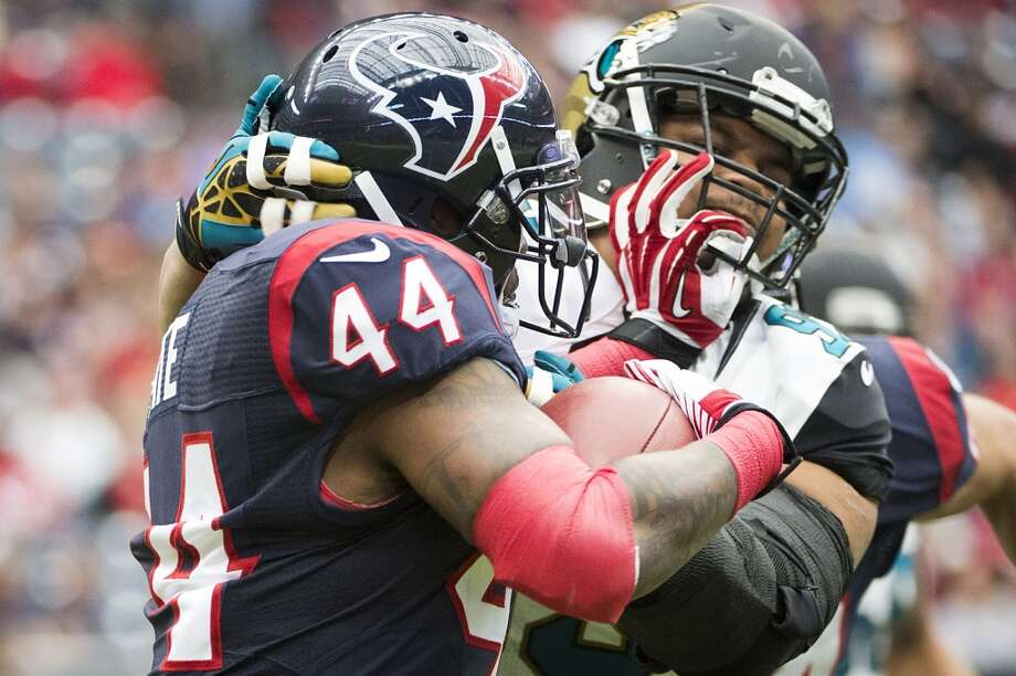Texans running back Ben Tate struggles for yards against Jaguars defensive end Tyson Alualu. Photo: Smiley N. Pool, Houston Chronicle