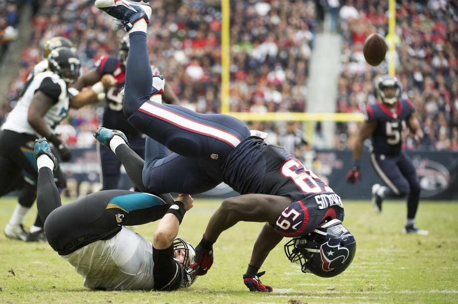 Jaguars quarterback Chad Henne (7) tries to get off a pass as he is hit by Texans linebacker Whitney Mercilus (59) during the first half. Henne was called for intentional grounding. Photo: Smiley N. Pool, Houston Chronicle