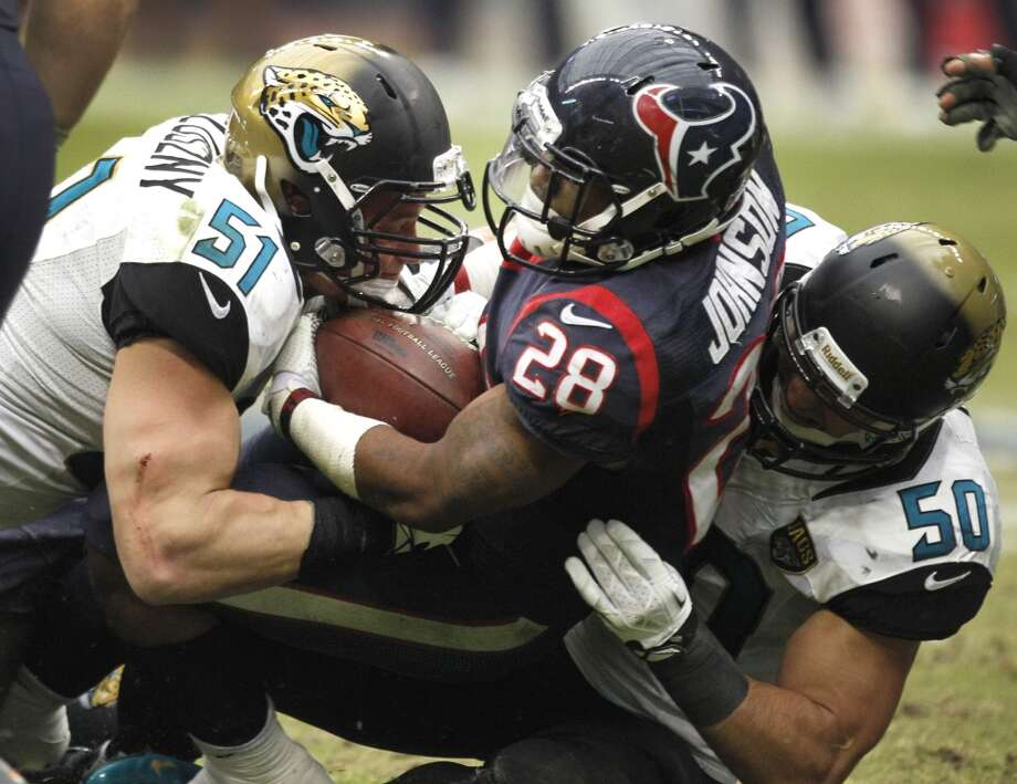 Texans running back Dennis Johnson is stopped short of the first down by Jaguars linebackers Paul Posluszny and Russell Allen on fourth-and-one during the fourth quarter. Photo: Brett Coomer, Houston Chronicle