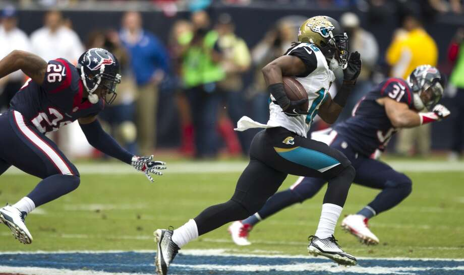 Jaguars wide receiver Ace Sanders (18) runs past Texans defensive backs Brandon Harris (26) and Shiloh Keo (31) for a 51-yard gain during the first quarter. Photo: Brett Coomer, Houston Chronicle