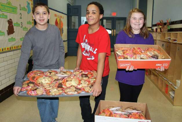 Students from St. Augustine's School in Troy, along with the St. Augustine's Parish Good Works Youth Ministry, donate canned goods, money and student-made baked cookies to the St. Vincent DePaul Food Pantry in Lansingburgh. (Submitted photo)