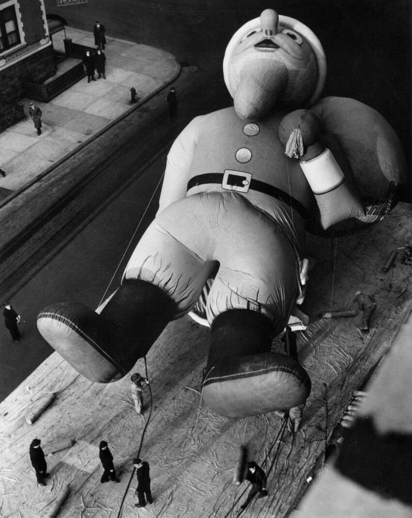 Workmen inflate a giant 45-foot Santa Claus with helium for the Macy's Parade, New York on Nov. 21, 1940. This annual procession is held every Thanksgiving by Macy's department store.