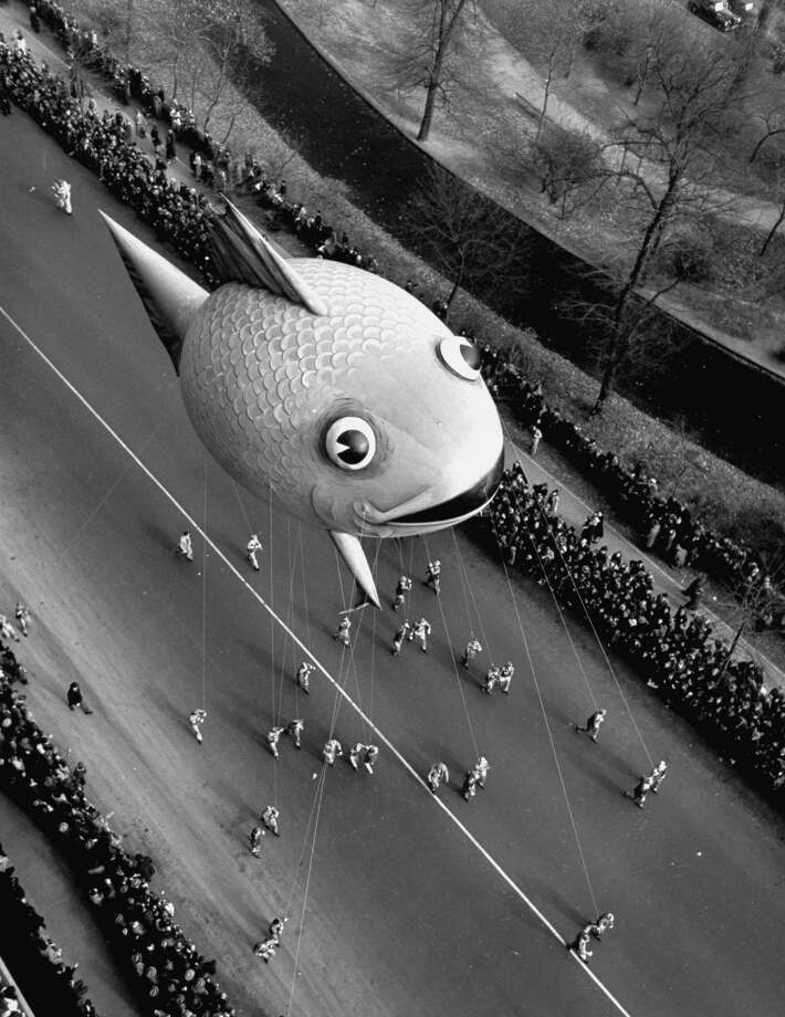 Crowds line the streets as a fish balloon floats by during the Macy's Thanksgiving Day Parade on Nov. 25, 1941. Photo: JOHN PHILLIPS, Getty Images / Time & Life Pictures Creative