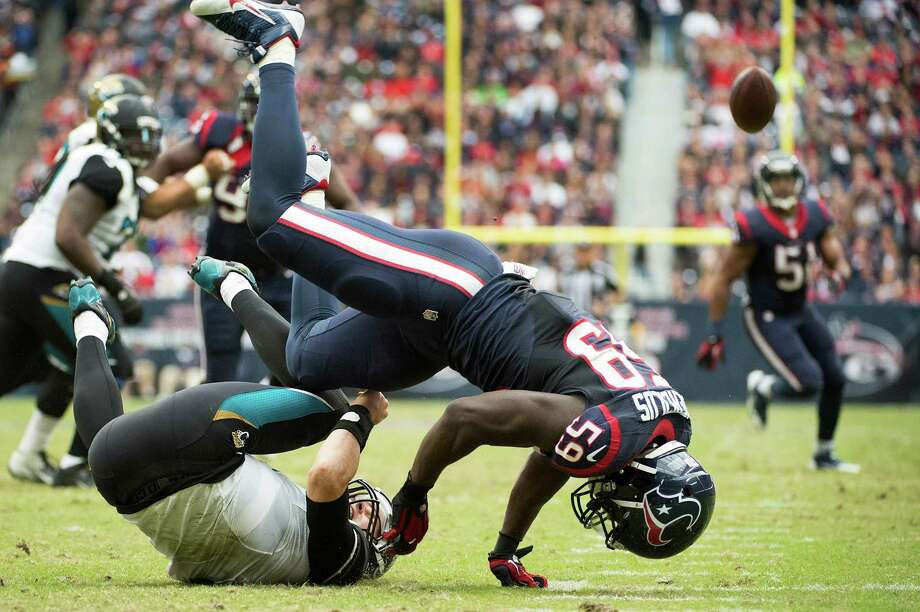 Linebacker Whitney Mercilus (59) brings down Jaguars quarterback Chad Henne on one of four sacks recorded by the Texans' defense on Sunday. Henne also was called for intentional grounding on the play, Photo: Smiley N. Pool, Staff / © 2013  Houston Chronicle