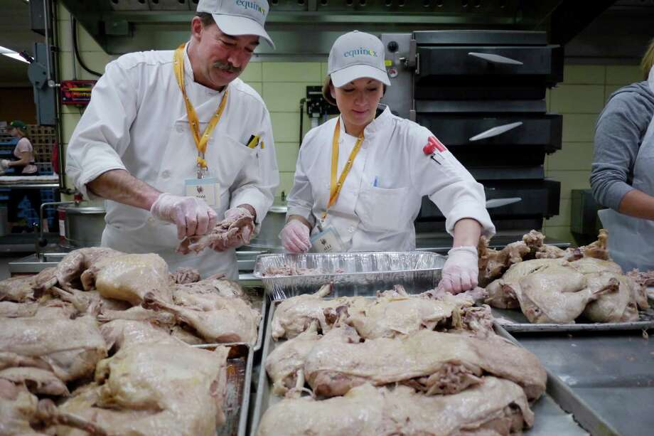 """Tom Tibbitts, left, volunteer head chef, and his daughter, Alli Tibbitts, who oversees all food prep safety, work on removing turkey meat from the bones at the State OGS kitchens in the Empire State Plaza on Sunday, Nov. 24, 2013 in Albany, NY.  Tom started volunteering about 30 years ago, coming one time just to give some cooking pointers to the cooks at the time.  """"That first time I went I took a walk from where we were cooking to the First Presbyterian Church were they would be feeding people the next day and in the park I saw people sleeping there so that they could be there the next day for the meal, it was all they had and I knew right then I had to keep coming back.""""  Alli began coming when her mom was pregnant with her and just kept becoming more involved every year after she was born.    (Paul Buckowski / Times Union) Photo: Paul Buckowski / 00024766A"""