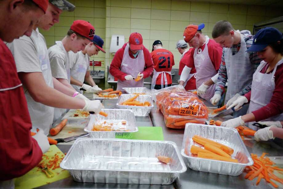 Members of the Maple Hill boy's basketball team peel carrots as they volunteer at the State OGS kitchens in the Empire State Plaza on Sunday, Nov. 24, 2013 in Albany, NY.  This is the third year the team has volunteered.   Some 3,600 volunteers will work over the four days preparing the food that will be boxed up and delivered to 9,500 people on Thanksgiving morning.  Equinox volunteers will also serve around 500 meals on Thanksgiving at First Presbyterian Church.  This is the 44th years of the community dinner.  Equinox is still in need of volunteer drivers to help deliver the meals and those interested can go to www.EquinoxInc.org to sign up.  Those in need of a meal for Thanksgiving can also go to the website to signup for the meal delivery.      (Paul Buckowski / Times Union) Photo: Paul Buckowski / 00024766A