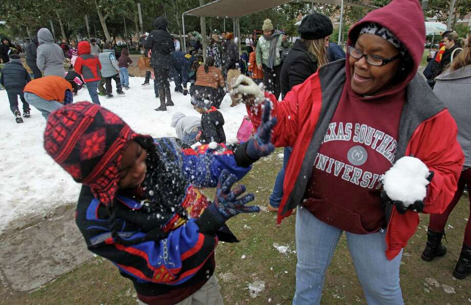 Tavaris Collins, 9, and his grandmother, Diane Campbell, play with snow during the Fire and ICE Carnival at Discovery Green, 1500 McKinney, Sunday, Nov. 24, 2013, in Houston.   Other events included fire-breathing art cars, music, ice carving, ice skating performances, and the opportunity to carve names in a 10-foot-wall of ice. Photo: Melissa Phillip, Houston Chronicle / © 2013  Houston Chronicle