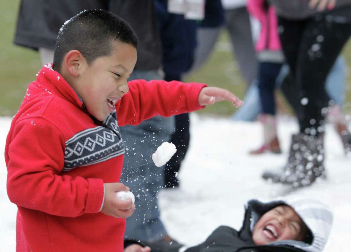 Aron Hernandez, 6, left, and his cousin, Joan Ventura, 5, right, play in snow during the Fire and ICE Carnival at Discovery Green, 1500 McKinney, Sunday, Nov. 24, 2013, in Houston. Other events included fire-breathing art cars, music, ice carving, ice skating performances, and the opportunity to carve names in a 10-foot-wall of ice.