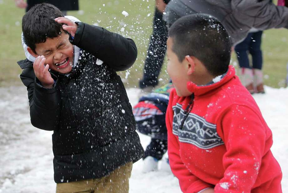 Joan Ventura, 5, left, and his cousin, Aron Hernandez, 6, play in snow during the Fire and ICE Carnival at Discovery Green, 1500 McKinney, Sunday, Nov. 24, 2013, in Houston.   Other events included fire-breathing art cars, music, ice carving, ice skating performances, and the opportunity to carve names in a 10-foot-wall of ice. Photo: Melissa Phillip, Houston Chronicle / © 2013  Houston Chronicle