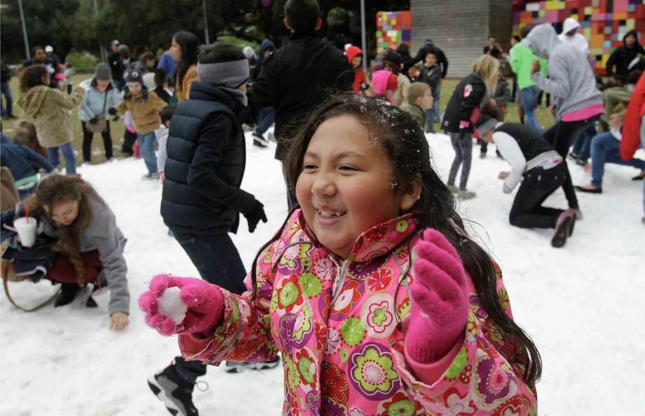 Lilly Montoya, 9, plays with snow during the Fire and ICE Carnival at Discovery Green, 1500 McKinney, Sunday, Nov. 24, 2013, in Houston.  Other events included fire-breathing art cars, music, ice carving, ice skating performances, and the opportunity to carve names in a 10-foot-wall of ice. Photo: Melissa Phillip, Houston Chronicle / © 2013  Houston Chronicle