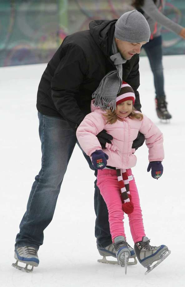 Nick Barjaktarevic helps his daughter, Mia Barjaktarevic, 4, skate for the first time at Discovery Green, 1500 McKinney, Sunday, Nov. 24, 2013, in Houston. The ice rink will be open daily through February 2, 2014. The ice rink which opened Saturday was part of the features for the Fire and ICE Carnival which including fire-breathing art cars, music, ice carving, ice skating performances, the opportunity to carve names in a 10-foot-wall of ice and playing in snow. Photo: Melissa Phillip, Houston Chronicle / © 2013  Houston Chronicle