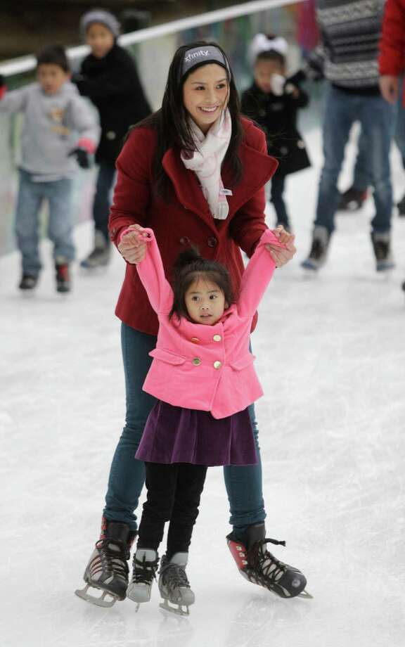 Mylene Pham helps her daughter, Emeline Pham, 4, skate for the first time during her birthday celebrate at Discovery Green, 1500 McKinney, Sunday, Nov. 24, 2013, in Houston. The ice rink will be open daily through February 2, 2014. The ice rink which opened Saturday was part of the features for the Fire and ICE Carnival which including fire-breathing art cars, music, ice carving, ice skating performances, the opportunity to carve names in a 10-foot-wall of ice and playing in snow. Photo: Melissa Phillip, Houston Chronicle / © 2013  Houston Chronicle