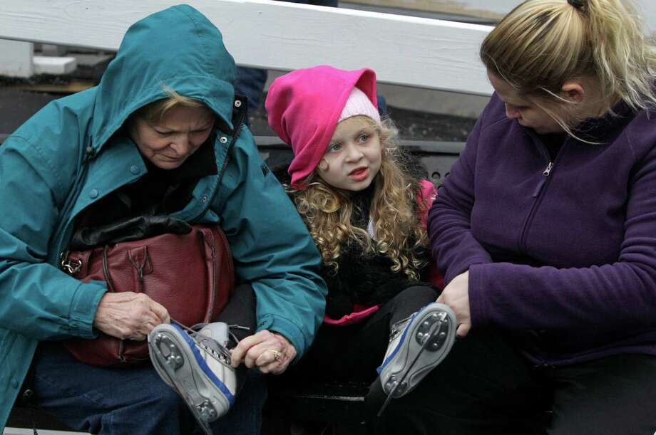 Chloe Ganze, 4, of Baytown has her ice skates tied by her grandmother, Ada Ganze, left, and her mother, Tiffany Ganze, right, at Discovery Green, 1500 McKinney, Sunday, Nov. 24, 2013, in Houston. The ice rink will be open daily through February 2, 2014. The ice rink which opened Saturday was part of the features for the Fire and ICE Carnival which including fire-breathing art cars, music, ice carving, ice skating performances, the opportunity to carve names in a 10-foot-wall of ice and playing in snow. Photo: Melissa Phillip, Houston Chronicle / © 2013  Houston Chronicle