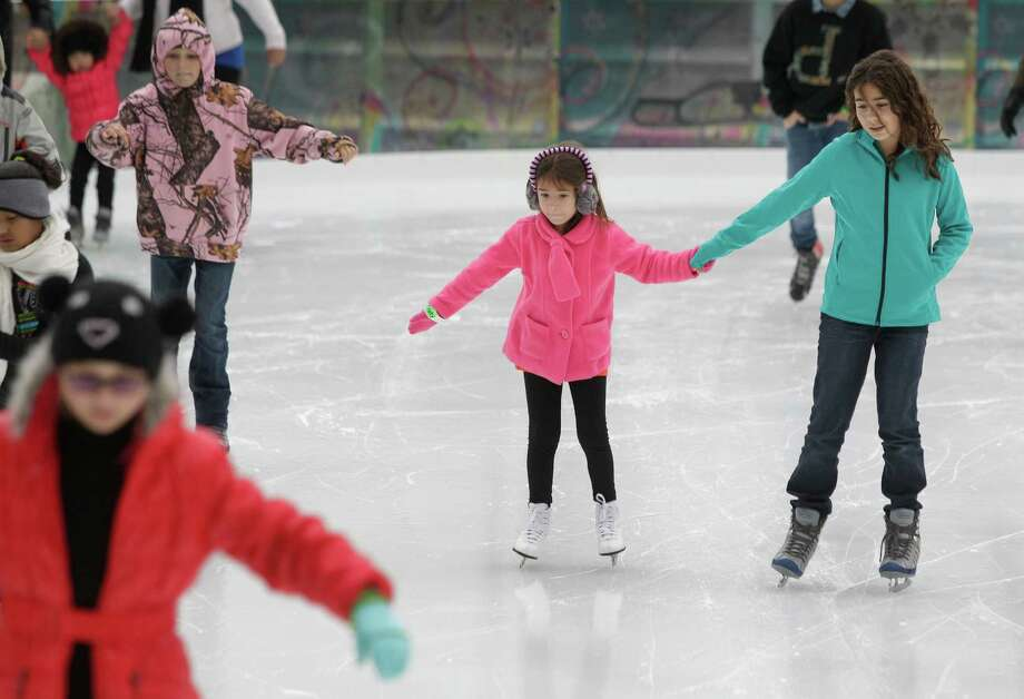 Elizabeth Perez, 5, left, and her sister, Emily Perez, 10, right, skate together at Discovery Green, 1500 McKinney, Sunday, Nov. 24, 2013, in Houston. The ice rink will be open daily through February 2, 2014. The ice rink which opened Saturday was part of the features for the Fire and ICE Carnival which including fire-breathing art cars, music, ice carving, ice skating performances, the opportunity to carve names in a 10-foot-wall of ice and playing in snow. Photo: Melissa Phillip, Houston Chronicle / © 2013  Houston Chronicle