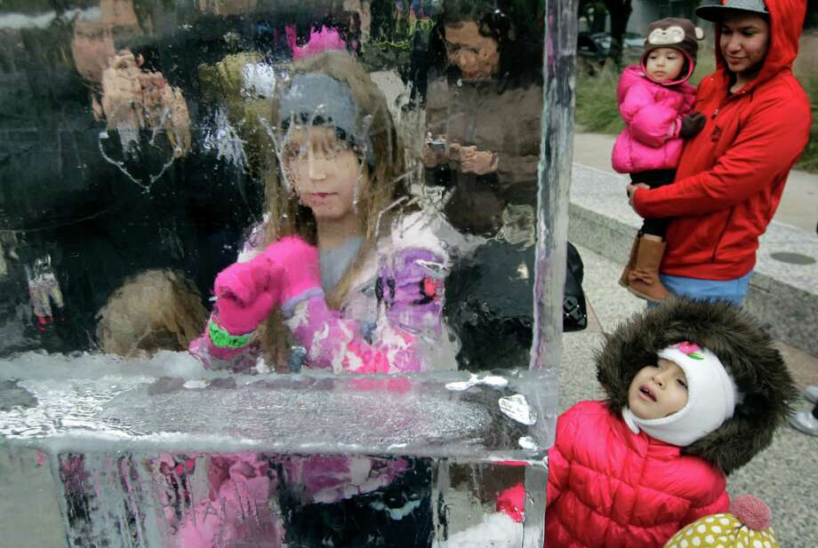 May Wimer, 8, left, of Nederland carves her name into a 10-foot wall of ice during the Fire and ICE Carnival at Discovery Green, 1500 McKinney, Sunday, Nov. 24, 2013, in Houston.  Other events included fire-breathing art cars, music, ice carving, ice skating performances, and playing in snow. Photo: Melissa Phillip, Houston Chronicle / © 2013  Houston Chronicle