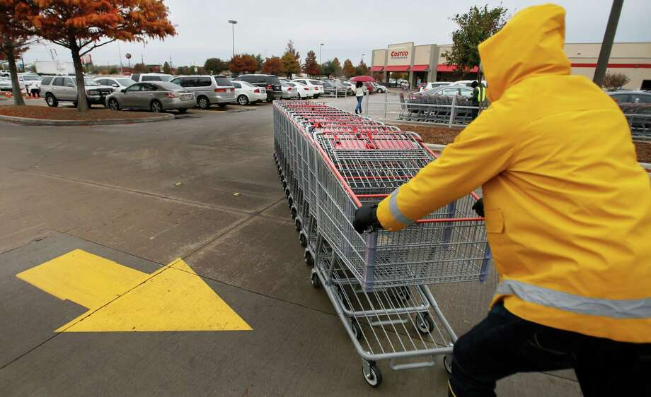 Cameron Bongo braves the drizzle and gusty winds to collect the shopping carts in the Costco parking lot off of US 75 in Plano, as an arctic cold front begins to move into the North Texas area on Sunday, November 24, 2013.  (Louis DeLuca/Dallas Morning News) Photo: Louis DeLuca, Staff Photographer / 00020033A
