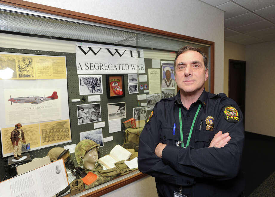 """Greenwich Police Officer Bill Romanello in front of the """"WWII, a Segregated War"""" display that he and the Connecticut Combat Team, a group of amateur military historians, put together at Greenwich Town Hall, as seen Friday. Photo: Bob Luckey / Greenwich Time"""