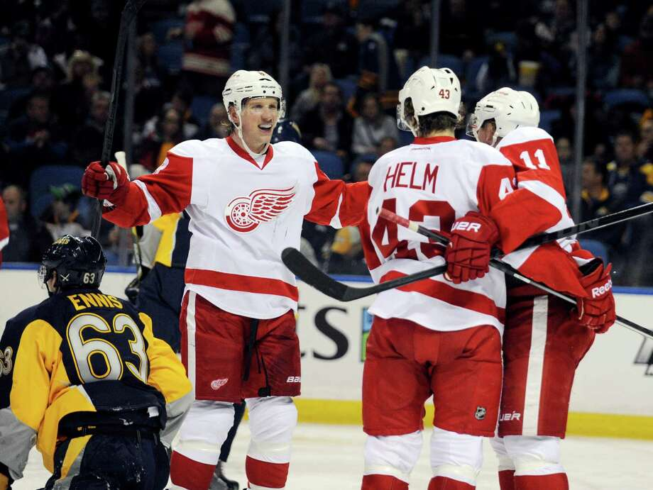 Buffalo Sabres' Tyler Ennis (63) passes a celebration by Detroit Red Wings' Justin Abdelkader (8), Darren Helm (43) and Daniel Alfredsson (11) after Helm scored  during the second period of an NHL hockey game in Buffalo, N.Y., Sunday, Nov. 24, 2013. (AP Photo/Gary Wiepert) ORG XMIT: NYGW104 Photo: Gary Wiepert / FR170498 AP