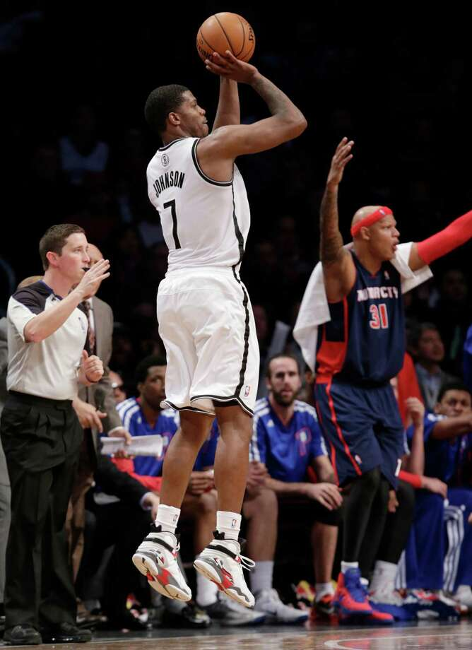 Brooklyn Nets guard Joe Johnson (7) shoots a three-pointer as Detroit Pistons forward Charlie Villanueva (31) yells out to his teammates in the second half of an NBA basketball game, Sunday, Nov. 24, 2013, in New York. (AP Photo/Kathy Willens) ORG XMIT: NYKW111 Photo: Kathy Willens / AP