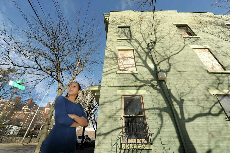 Dannielle Hille, who lives down the street from a vacant building across from the governor's mansion, stands in front of the boarded up building at 161 Eagle Street on Thursday Nov. 21, 2013 in Albany, N.Y. (Michael P. Farrell/Times Union) Photo: Michael P. Farrell / 00024740A