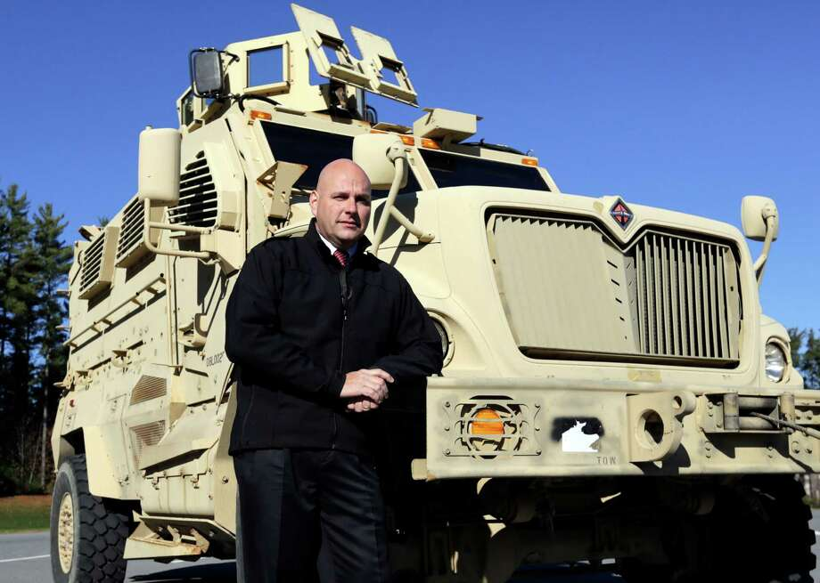 Warren County Undersheriff Shawn Lamouree poses in front of the department's mine resistant ambush protected vehicle, or MRAP, on Wednesday, Nov. 13, 2013, in Queensbury, N.Y. For police and sheriff's departments, which have scooped up 165 of the mine-resistant ambush-protected vehicles, or MRAPS, since they became available this summer, the price and the ability to deliver shock and awe while serving warrants or dealing with hostage standoffs was just too good to pass up. (AP Photo/Mike Groll) ORG XMIT: NYMG204 Photo: Mike Groll / AP