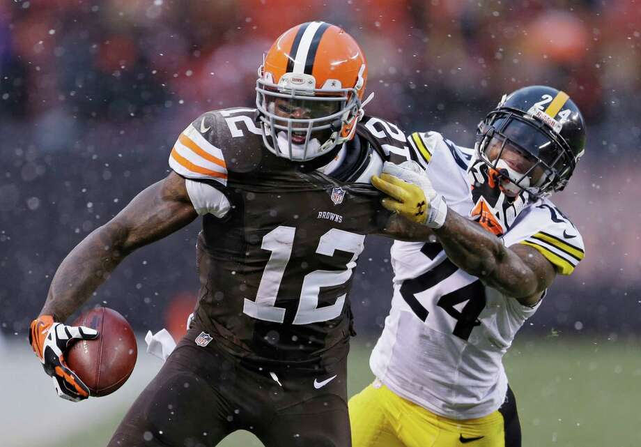 Cleveland receiver Josh Gordon (12) makes Pittsburgh cornerback Ike Taylor pay to bring him down after a fourth-quarter catch. Gordon had 14 receptions for a team-record 237 yards in the Browns' 24-11 loss. Photo: Tony Dejak, STF / AP