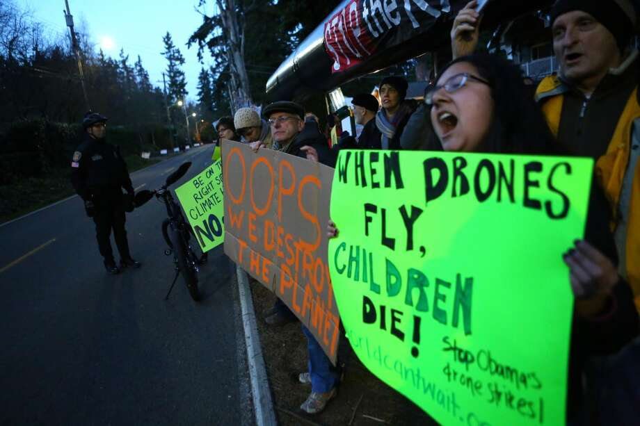 Protesters opposed to the Keystone XL pipeline and military drones wait for the motorcade of President Barack Obama in northwest Seattle. Photo: JOSHUA TRUJILLO, SEATTLEPI.COM