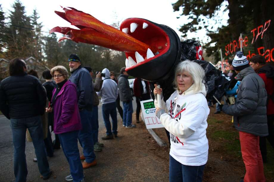 Mary Hath Spokane works with other protesters to carry an inflatable replica of a pipeline as groups opposed to the Keystone XL pipeline make their voices heard outside a fundraiser attended by U.S. President Barack Obama. Photo: JOSHUA TRUJILLO, SEATTLEPI.COM