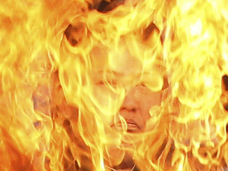 A portrait of North Korean leader Kim Jong Un burns after activists set it on fire during a rally to mark the the third anniversary of North Korea's artillery attack on the Yeonpyeong island, in Seoul, South Korea, Saturday, Nov. 23, 2013. Four people, including two marines and two civilians, were killed by North Korea's attack. (AP Photo/Ahn Young-joon) Photo: Ahn Young-joon, Associated Press