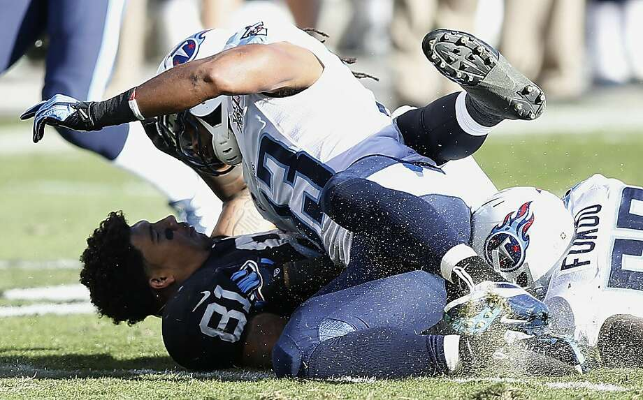 Oakland Raiders tight end Mychal Rivera (81) loses his helmet as he is hit by Tennessee Titans free safety Michael Griffin (33) during the second quarter of an NFL football game in Oakland, Calif., Sunday, Nov. 24, 2013.  Rivera left the game after being injured on the play. (AP Photo/Beck Diefenbach) Photo: Beck Diefenbach, Associated Press
