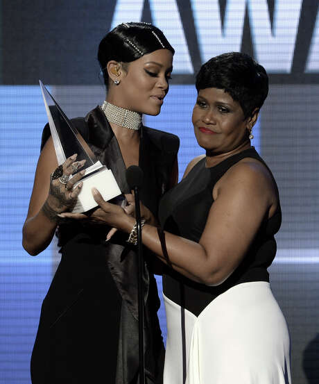 Rihanna, left, accepts the first AMA Icon Award from her mother Monica Fenty during the American Music Awards in Los Angeles Sunday night. Photo: Kevin Winter, Staff / 2013 Getty Images