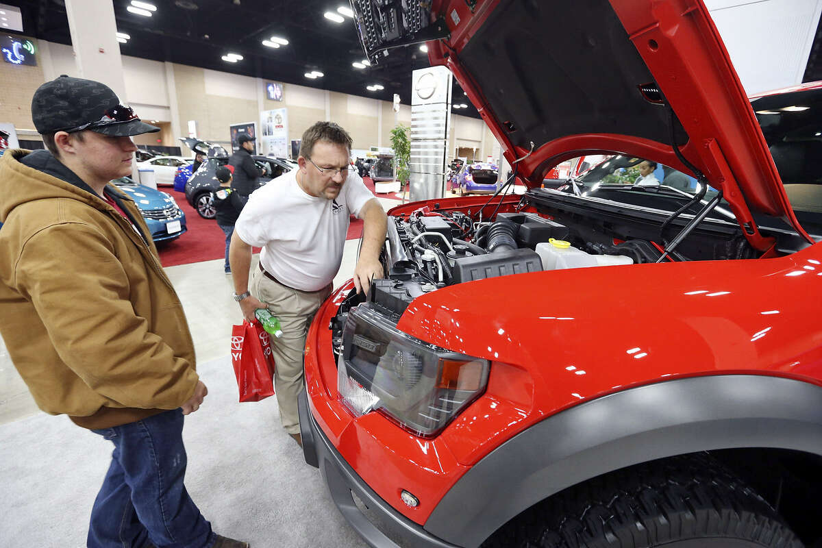 Spencer Westeren (left) and his father, Dale Westeren, look at a 2013 Ford F-150 SVT Raptor pickup at the San Antonio Auto & Truck Show, spiced by the appearance of Spurs players, at the Convention Center.