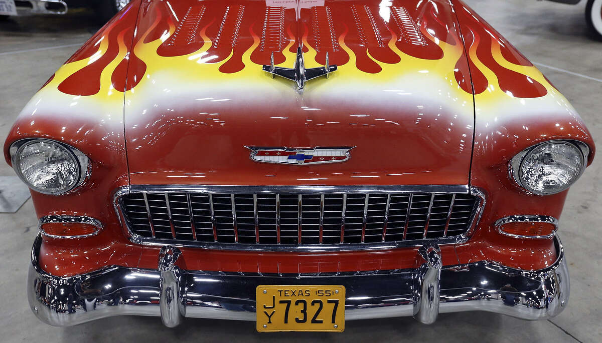 A flame-tempered 1955 Chevrolet 150 Sedan is displayed at the show. When asked how the show has changed in the five years since her family started attending, a mother's little boy interjects,