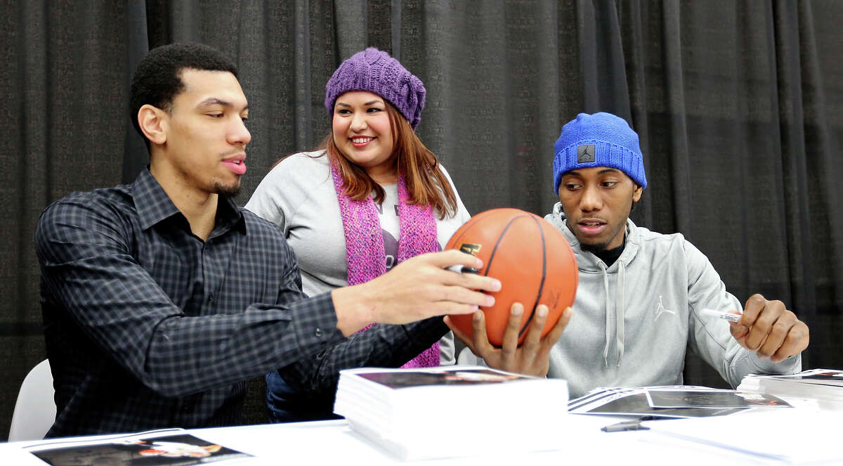Kristine Flores (center) is all smiles as she has a basketball autographed by Spurs player Danny Green (left) and Kawhi Leonard Sunday Nov. 24, 2013 during the 2013 San Antonio Auto & Truck Show at the Henry B. Gonzalez Convention Center.