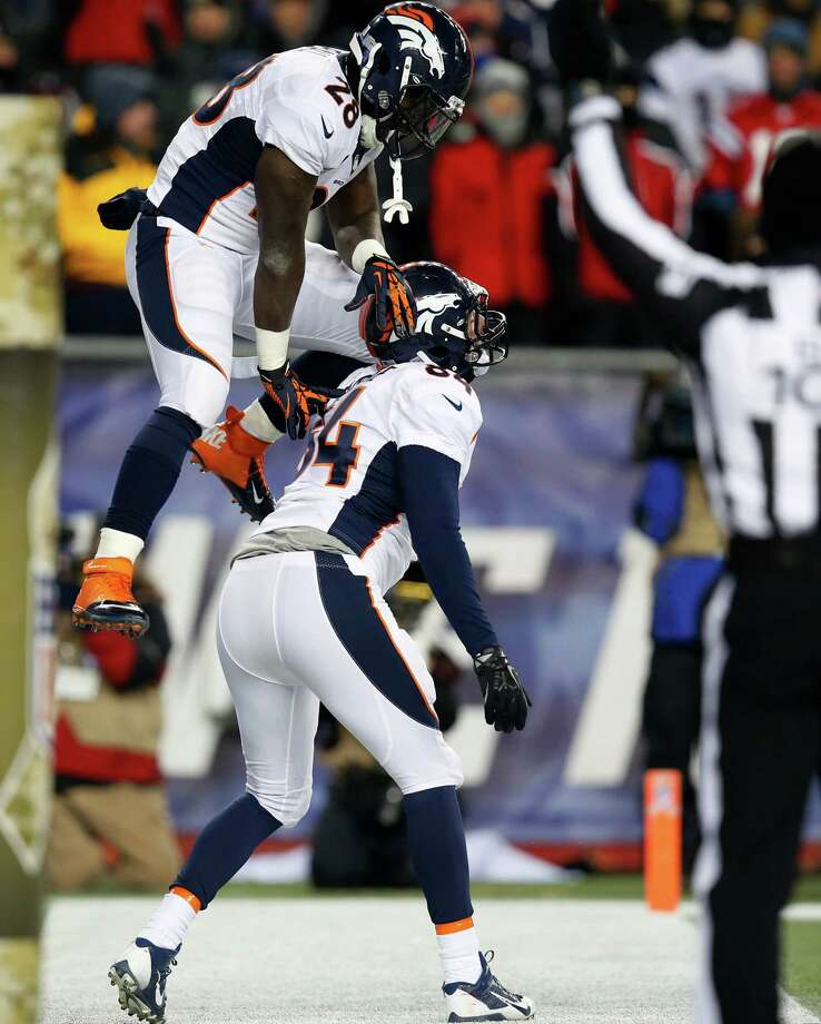 Denver Broncos Montee Ball, top, celebrates a touchdown catch by Jacob Tamme (84) in the second quarter of an NFL football game against the New England Patriots Sunday, Nov. 24, 2013, in Foxborough, Mass. (AP Photo/Elise Amendola) Photo: Elise Amendola, Associated Press / AP