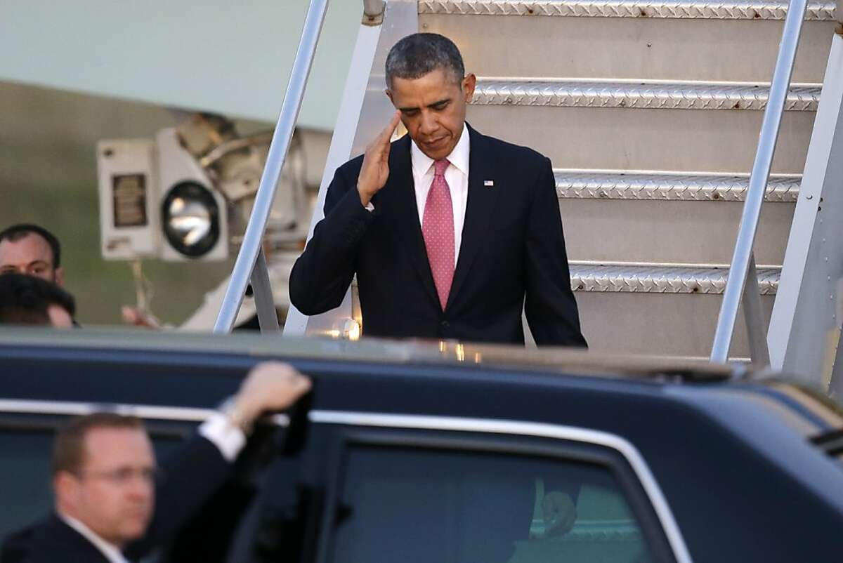 President Barack Obama salutes after arriving Sunday, Nov. 24, 2013, at Seattle-Tacoma International Airport in Seattle. Obama is traveling on a three day West Coast swing to Seattle, San Francisco and Los Angeles that will feature a bit of official business but mostly fundraising for the Democratic party. (AP Photo/Elaine Thompson)