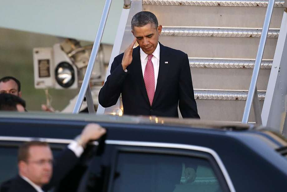President Barack Obama salutes after arriving Sunday, Nov. 24, 2013, at Seattle-Tacoma International Airport in Seattle. Obama is traveling on a three day West Coast swing to Seattle, San Francisco and Los Angeles that will feature a bit of official business but mostly fundraising for the Democratic party. (AP Photo/Elaine Thompson) Photo: Elaine Thompson, Associated Press