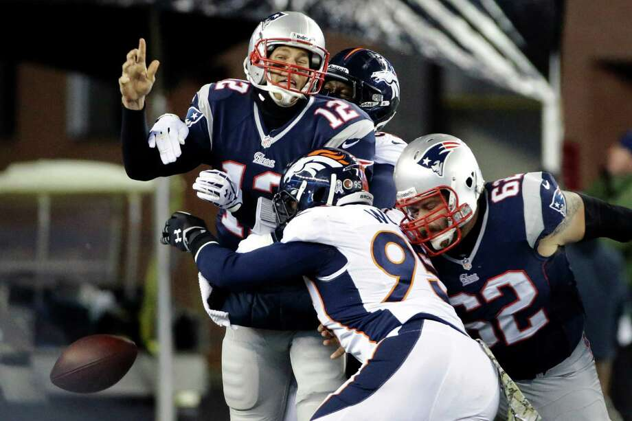Patriots quarterback Tom Brady coughs up the ball while being sacked by Broncos linebacker Von Miller, rear, as defensive end Derek Wolfe also closes in during a mistake-filled first half for New England on Sunday night. Photo: Stephan Savoia, STF / AP