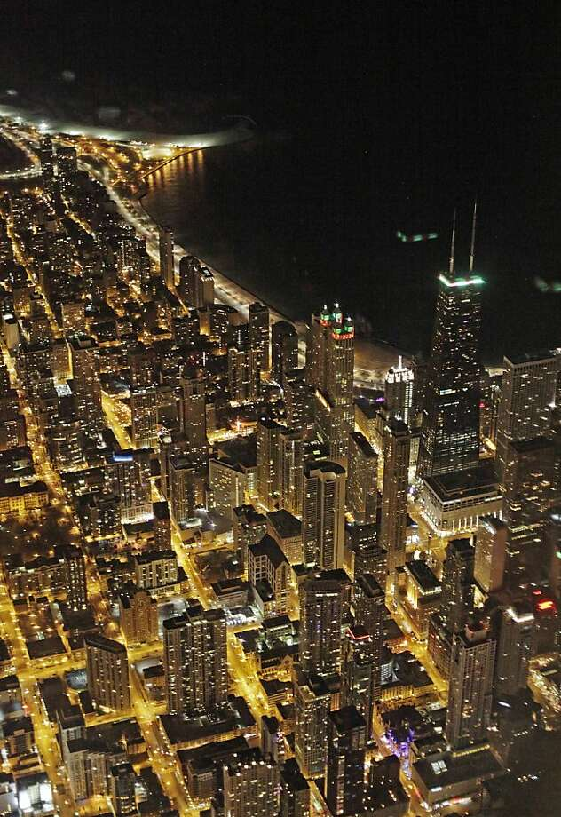 An aerial view at night of the downtown Chicago skyline is seen Sunday, Nov. 24, 2013. An Arctic air mass is expected to chill much of the Central Plains and the East Coast through Monday with wind-chill temperatures dropping into the single digits overnight in some places. (AP Photo/Kiichiro Sato) Photo: Kiichiro Sato, Associated Press