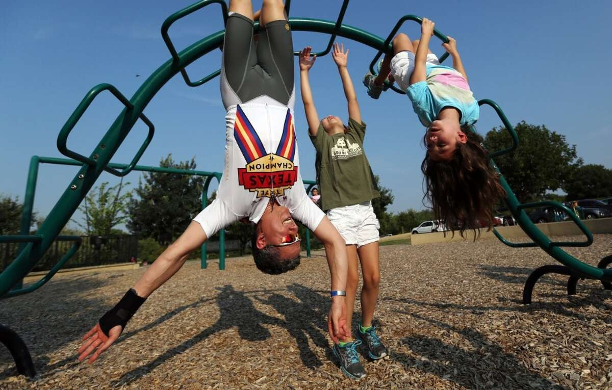 Dr. Ken Adams gets a workout playing with his daughters Isabelle, center, and Katherine at a Dallas playground.
