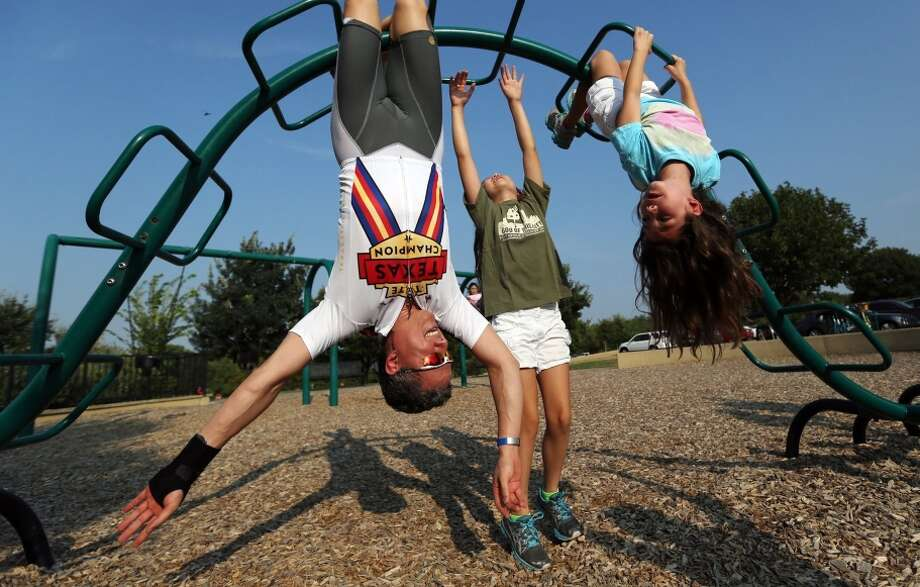 Dr. Ken Adams gets a workout playing with his daughters Isabelle, center, and Katherine at a Dallas playground. Photo: Ricky Moon / McClatchy-Tribune News Service / Dallas Morning News