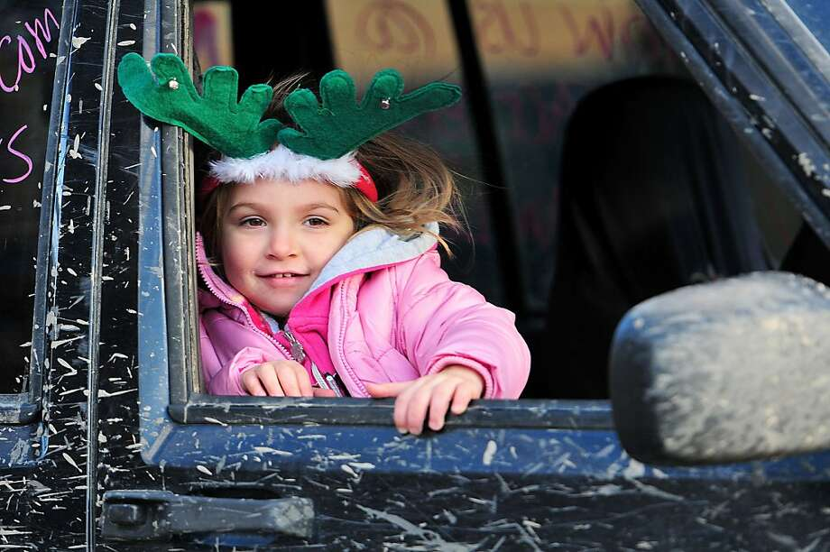 A young girl smiles out the window of a mud covered jeep, Sunday Nov. 24, 2013,  during the third annual West Side Santa Parade in Forty Fort, Pa. (AP Photo/ Citizens' Voice, Andrew Krech) Photo: Andrew Krech, Associated Press