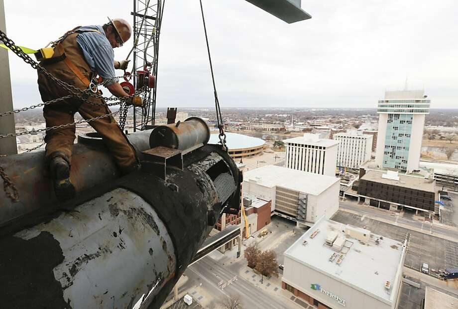 David Mitchell, an iron worker with Belger Cartage Service, Inc., works to remove a 16,000-pound air conditioning unit from the 19th floor of a downtown Wichita, Kan. building on Sunday, Nov. 24, 2013. Workers slowly pushed it out using skates and wenches and then a crane with a 270-foot boom arm lowered it to the ground. (AP Photo/The Wichita Eagle, Jaime Green) Photo: Jaime Green, Associated Press