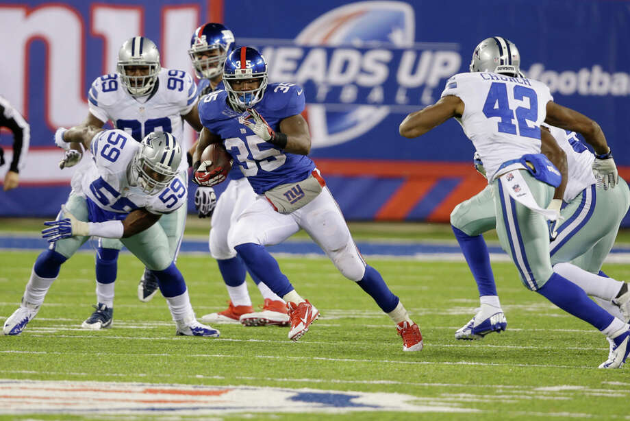 New York Giants running back Andre Brown (35) rushes as Dallas Cowboys free safety Barry Church (42) pursues him during the second half of an NFL football game, Sunday, Nov. 24, 2013, in East Rutherford, N.J. (AP Photo/Seth Wenig) Photo: Seth Wenig, Associated Press / AP