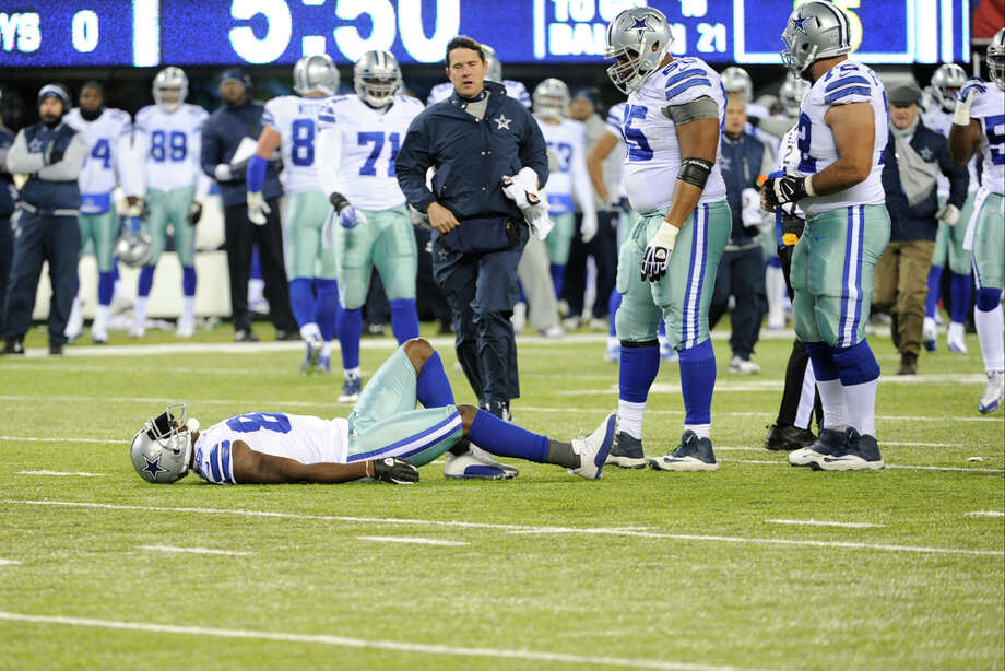 A trainer approaches Dez Bryant (88) after Bryant was hurt during the first half of an NFL football game against the New York Giants Sunday, Nov. 24, 2013, in East Rutherford, N.J. (AP Photo/Bill Kostroun) Photo: Bill Kostroun, Associated Press / FR51951 AP